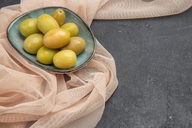 Vista frontale ravvicinata di olive verdi fresche naturali su un asciugamano piegato a metà sul lato destro su sfondo nero black
