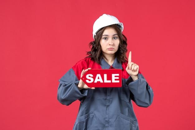 Vista frontale ravvicinata della lavoratrice nervosa in uniforme che indossa elmetto che mostra l'icona di vendita e rivolto verso l'alto sulla parete rossa isolata