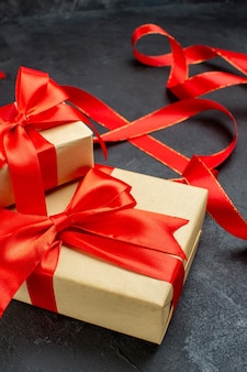 Вид спереди крупным планом красивых подарков с красной лентой на темном фоне