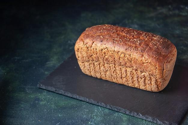 混合色の苦しめられた背景の上の黒い板の上の黒いパンの正面の拡大図