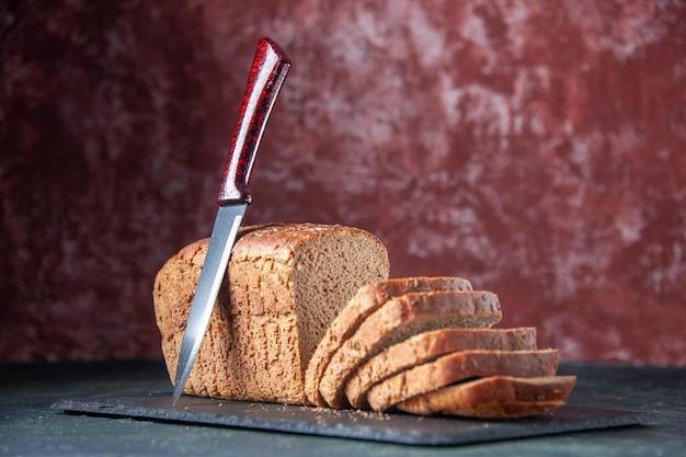 混合色の苦しめられた背景の暗い色のボード上の黒いパンのスライスナイフの正面の拡大図