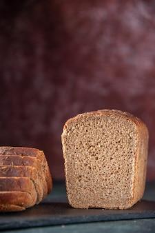 混合色の苦しめられた背景の上の黒い木製トレイの黒いパンのスライスの正面の拡大図