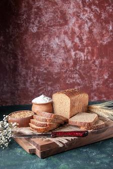混合色の背景のまな板に裸の色のタオルスパイク花の黒いパンのスライスの正面の拡大図