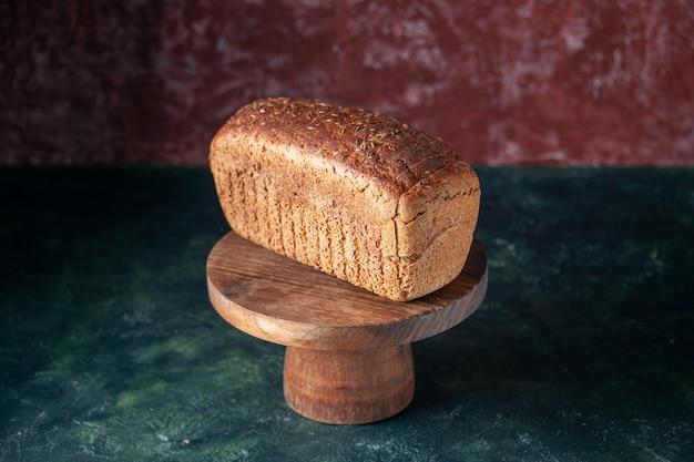 空きスペースと混合色の苦しめられた背景に木の板の黒いパンのスライスの正面の拡大図