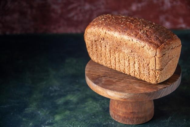 空きスペースのある混合色の苦しめられた背景の左側にある木の板の黒いパンのスライスの正面の拡大図