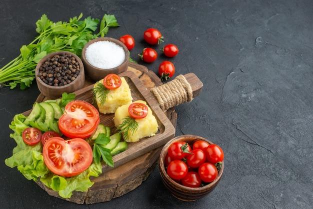 まな板の上に刻んだ新鮮な野菜のチーズと黒い表面にスパイスの緑の束を正面から見る