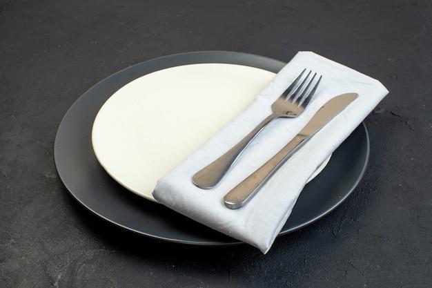 어두운 색의 흰색 냅킨에 있는 칼 붙이와 검정색 배경에 다른 크기의 흰색 빈 접시의 전면 닫기 보기