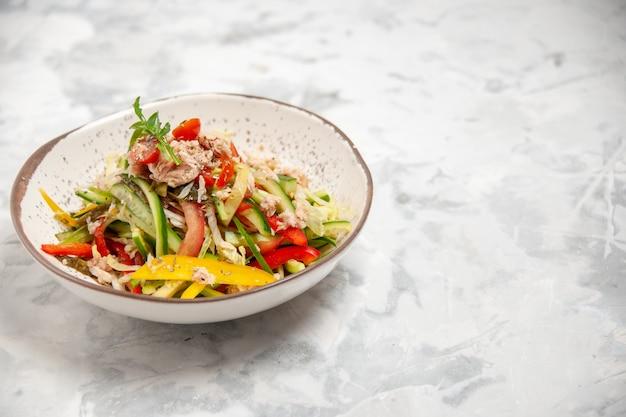 여유 공간이있는 스테인드 흰색 표면의 오른쪽에 야채와 함께 맛있는 치킨 샐러드의 전면 닫기보기