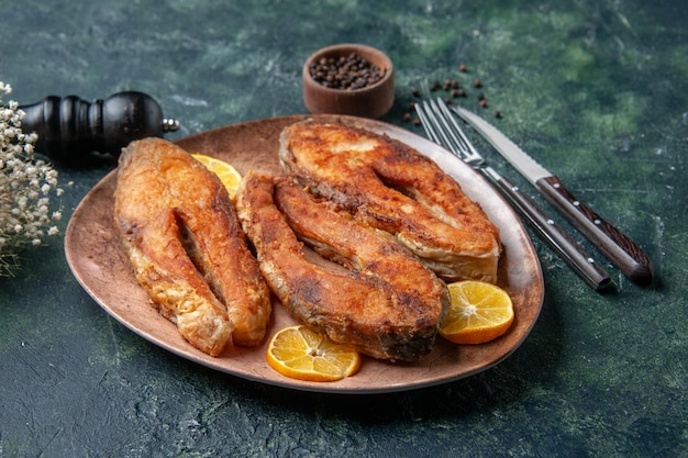 空きスペースのあるミックスカラーテーブルの茶色のプレートペッパーにおいしい揚げ魚とレモンスライスの正面の拡大図