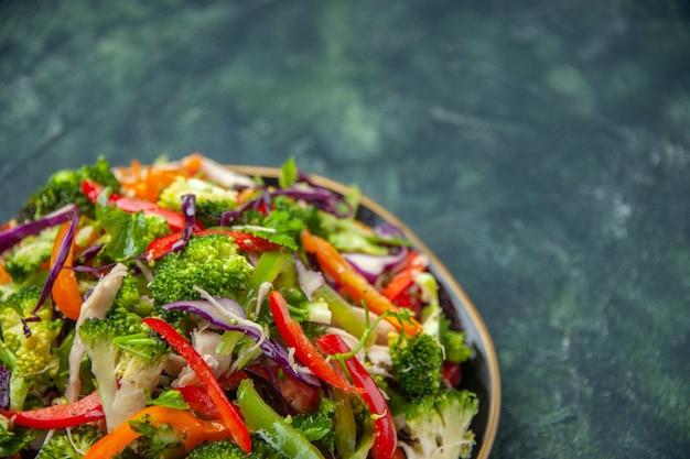 暗い背景にさまざまな新鮮な野菜とプレートのおいしいビーガンサラダの正面の拡大図