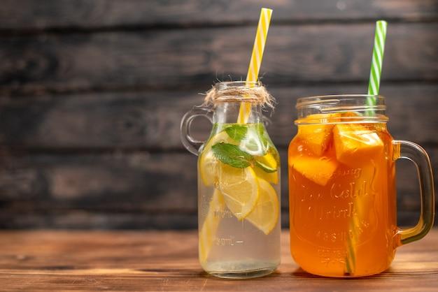 Вид спереди крупным планом на свежую воду для детоксикации и фруктовый сок, подаваемый с тюбиками с левой стороны на коричневом фоне