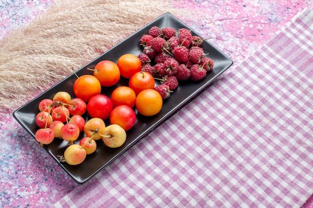 분홍색 표면에 검은 형태 내부 신선한 과일의 전면 가까이보기