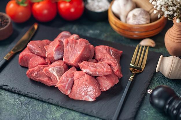 木の板にセットされた新鮮な生の刻んだ肉とカトラリーの正面の拡大図