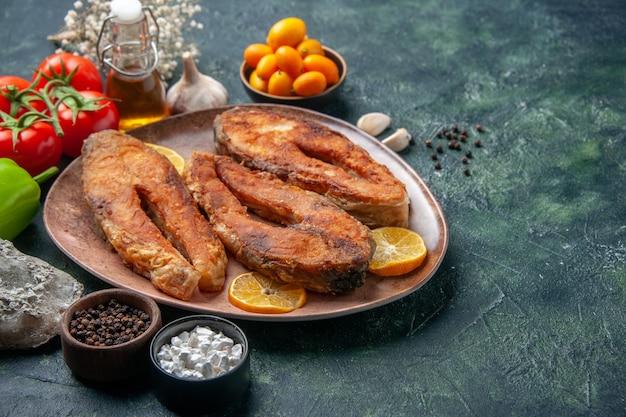茶色のプレートに揚げた魚とレモンスライスの正面の拡大図スパイストマトオイルボトルのミックスカラーテーブルに空きスペースがあります
