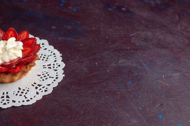 어두운 표면에 얇게 썬 과일과 함께 작은 크림 케이크의 전면 닫기보기