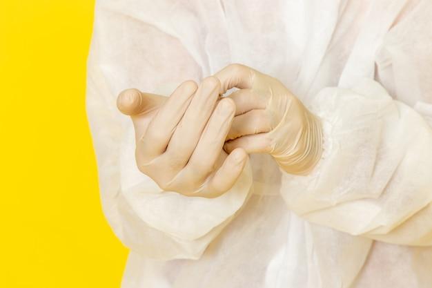 特別な防護服を着て、黄色の壁に手袋を着用したマスクを持つ男性の科学者の正面の拡大図