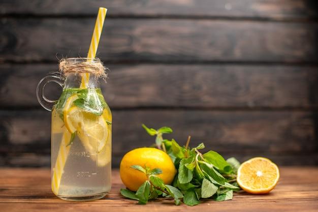 갈색 배경에 튜브 민트와 오렌지와 함께 제공되는 자연적인 신선한 해독 물의 전면 닫기보기