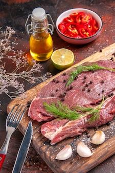 Вид спереди крупным планом красного мяса на деревянной разделочной доске и чесночной зеленой вилки и ножа нарезанного перца на темном фоне