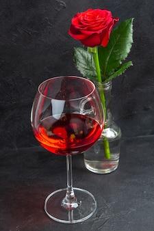 黒の背景に水と赤ワインで満たされた花瓶の赤いバラの正面近景