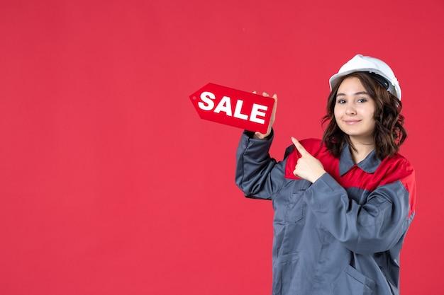 Крупным планом вид спереди улыбающейся работницы в униформе в каске и указывающей на значок продажи на изолированной красной стене