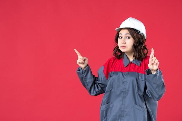 Крупным планом вид удивленной женщины-строителя в униформе с каской и делающей жест, скрещивающий пальцы на изолированной красной стене