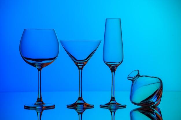Вид спереди крупным планом на различные виды пустых стеклянных кубков, стоящих на синей поверхности