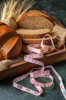 Вид спереди целиком и нарезанный свежий черный хлеб на полотенце в коричневом деревянном подносе на поверхности темных цветов