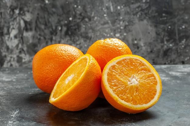 어두운 배경에 두 줄로 늘어선 전체 및 절단된 천연 유기농 신선한 오렌지의 전면 닫기
