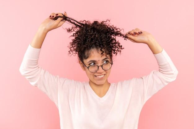 ピンクの髪で遊んでいる若い女性の正面のクローズ