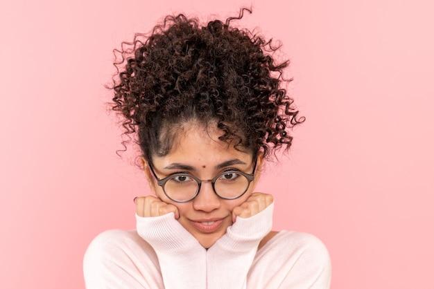 Вид спереди крупным планом молодой женщины, улыбаясь на розовом