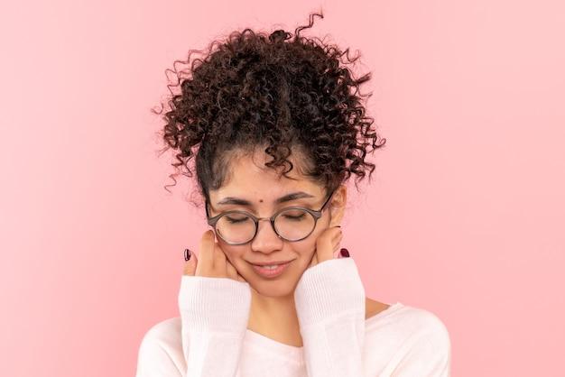 Вид спереди крупным планом молодой женщины с закрытыми глазами на розовом