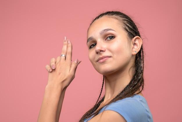 Вид спереди крупным планом молодой девушки в позе, держащей пистолет на розовом