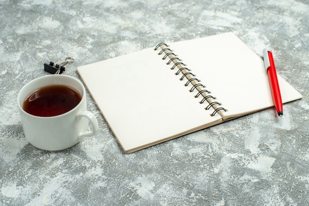 Front close view of open spiral notebook with pen and a cup of tea on gray background