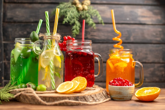 Front close view of organic fresh juices in bottles served with tubes and fruits on a wooden cutting board on a brown table