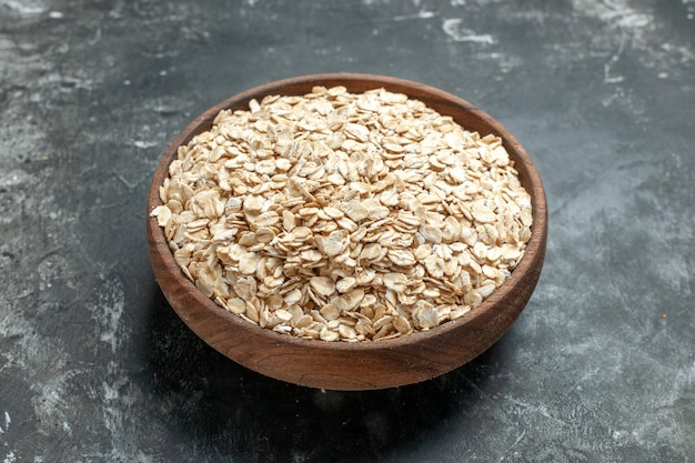 Front close view of organic oat bran in a brown wooden pot on dark background