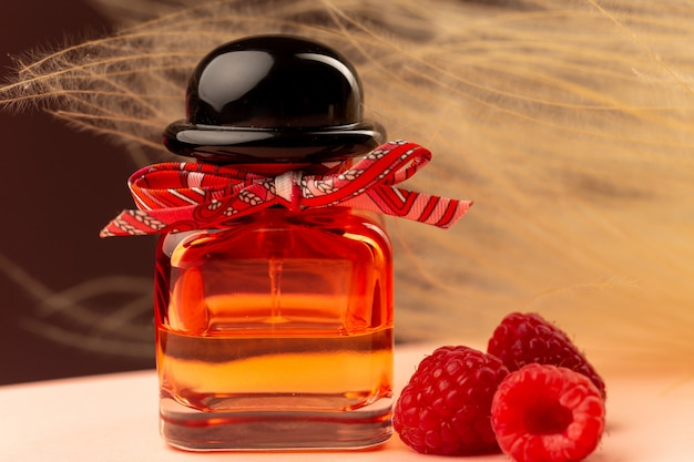 Front close view raspberry smelling perfume inside flask on the purple surface