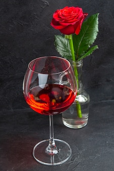 Front close view of red rose in a vase filled with water and red wine on a black background