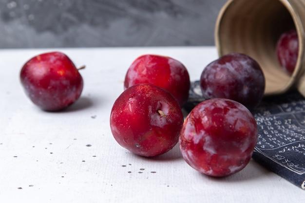Prugne acide rosse di vista vicina della parte anteriore fresche e mature da ogni parte dello scrittorio bianco