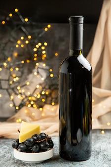 Vista frontale ravvicinata della bottiglia di vino rosso per la celebrazione della famiglia servita con frutta in un vaso bianco su sfondo scuro