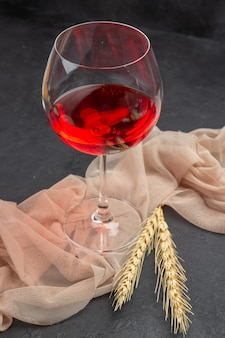 Front close view of red wine in a a glass goblet on a towel on black background