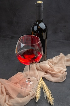 Front close view of red wine in a a glass goblet on a towel and bottle on black background