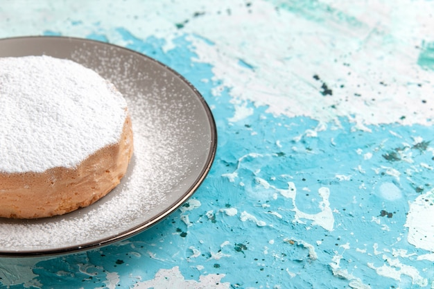 Front close view round cake with sugar powder inside plate on light blue surface cake bake biscuit sugar sweet tea color