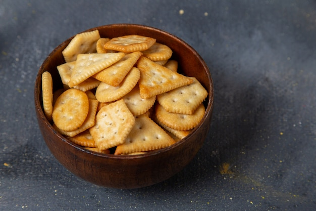 Front close view salted crackers inside brown plate on the grey surface