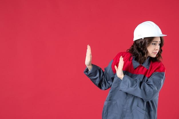 Vista ravvicinata anteriore del costruttore femminile spaventato in uniforme con il cappello duro sulla parete rossa isolata