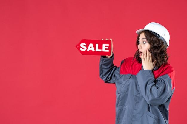 Vista frontale ravvicinata della lavoratrice scioccata in uniforme che indossa elmetto e che indica il segno di vendita sulla parete rossa isolata
