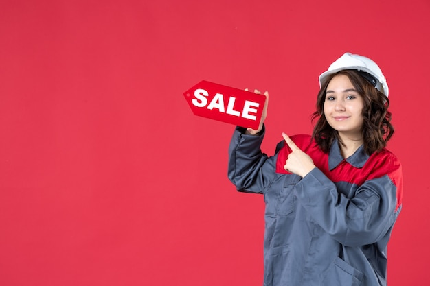 Vista frontale ravvicinata della lavoratrice sorridente in uniforme che indossa elmetto e che indica l'icona di vendita sulla parete rossa isolata
