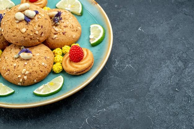 Biscotti di zucchero di vista ravvicinata anteriore con fette di limone sulla torta dolce del biscotto della torta di superficie grigia