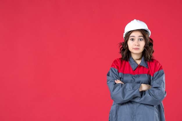 Front close view of surprised female builder in uniform with hard hat crossing her arms on isolated red wall