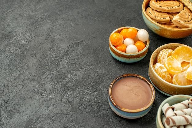 暗いテーブルの上のキャンディーと正面のクローズビューの甘いクッキークッキービスケット甘い