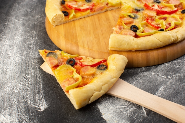 Front close view tasty cheesy pizza with red tomatoes, black olives, bell peppers and sausages